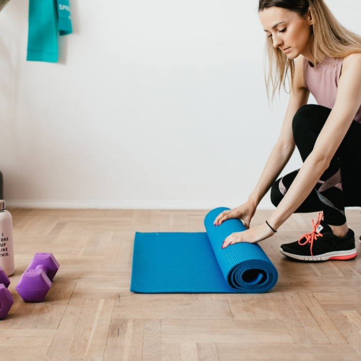 Lady rolling work out mat at home